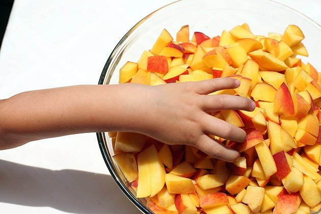 my boy's hand picking up diced peaches