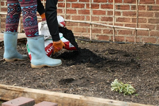 Adding garden soil to the garden bed.