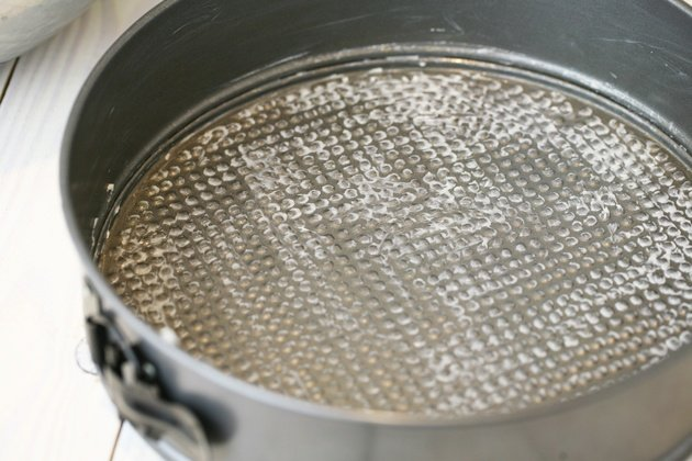 Coating a spring pan in butter.