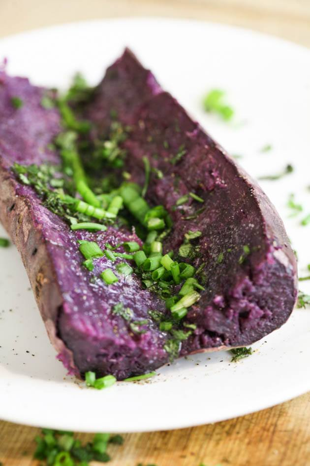 Seasoning the baked purple sweet potato with the greens and butter.