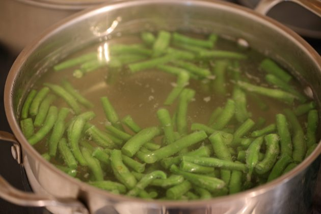 Blanching beans in a pot of boiling water.