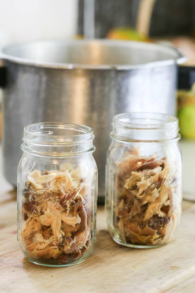 Packing pint jars with chicken meat.