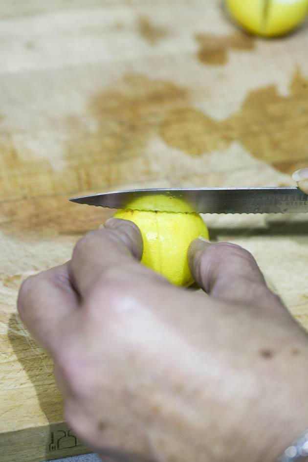 Slicing lemons into quarters.