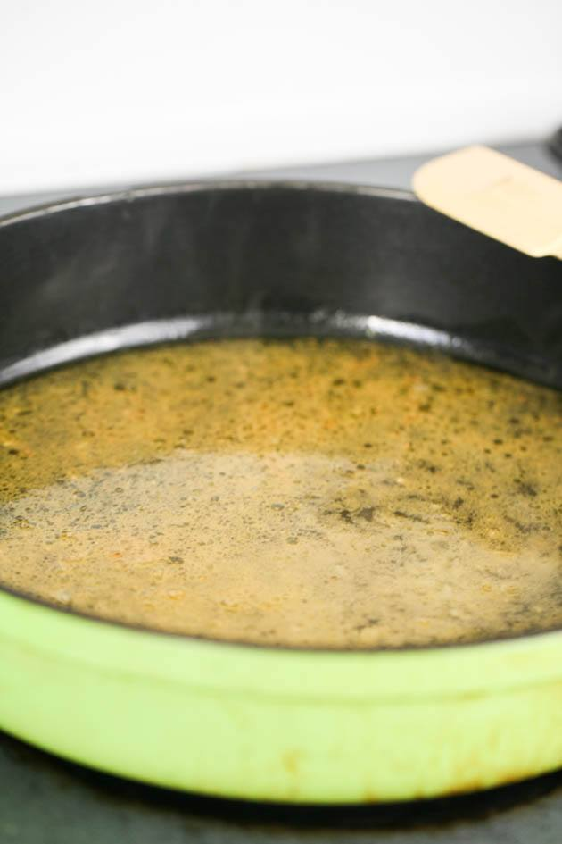 Adding the chicken stock to the pot.