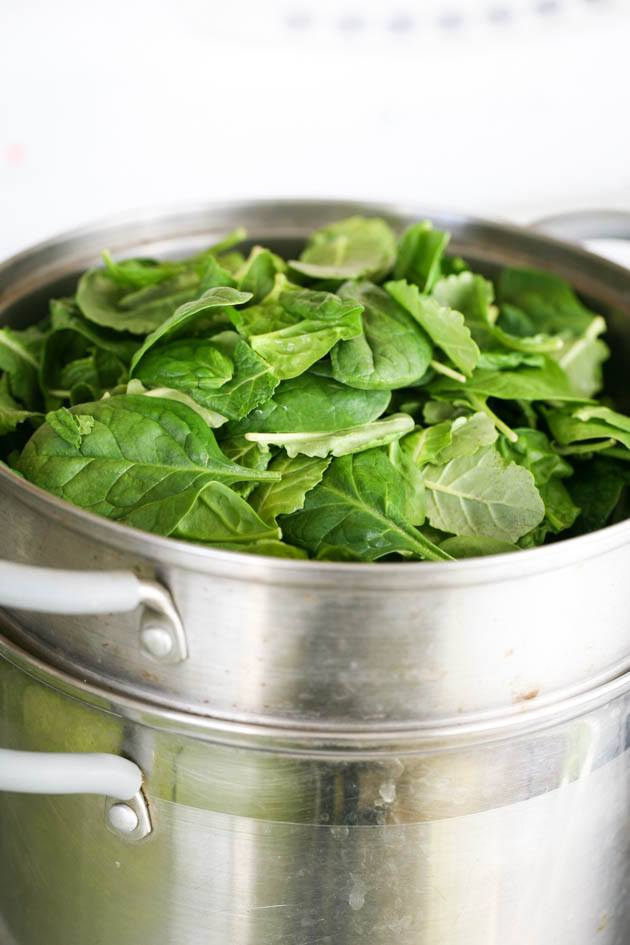 Adding the spinach to the pot.