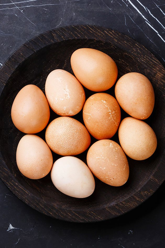 Guinea fowl eggs in a wooden bowl.