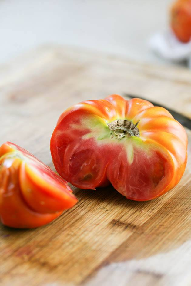 Cutting the damaged part of the tomato.