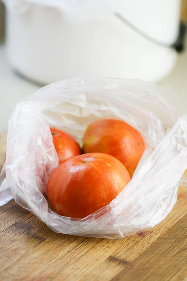 Whole tomatoes in a bag ready for freezing.