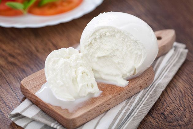 Homemade Mozzarella cheese on a wooden cutting board.
