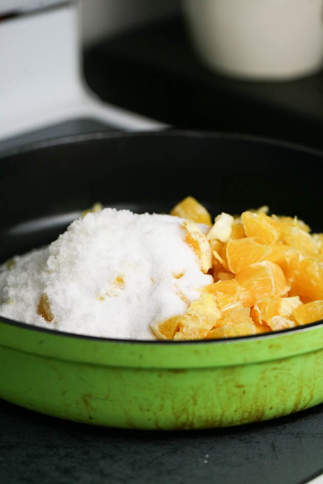 Sugar and oranges in a jam pan before cooking.
