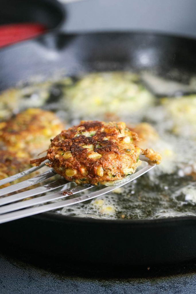 Flipping the fritters to fry on their other side.