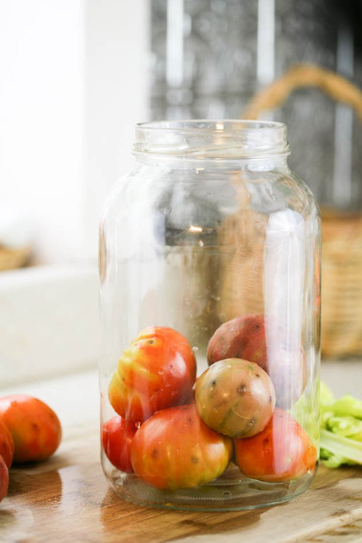 Adding tomatoes to the jar.
