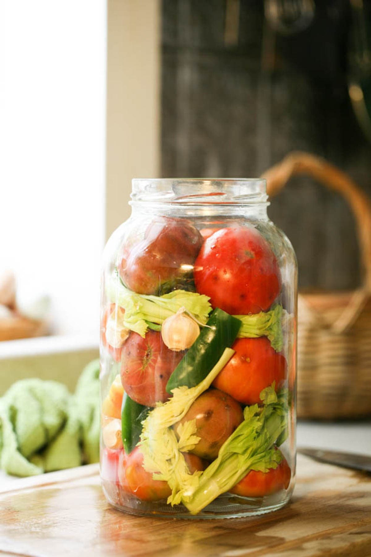 Filling the jar to the top with tomatoes.
