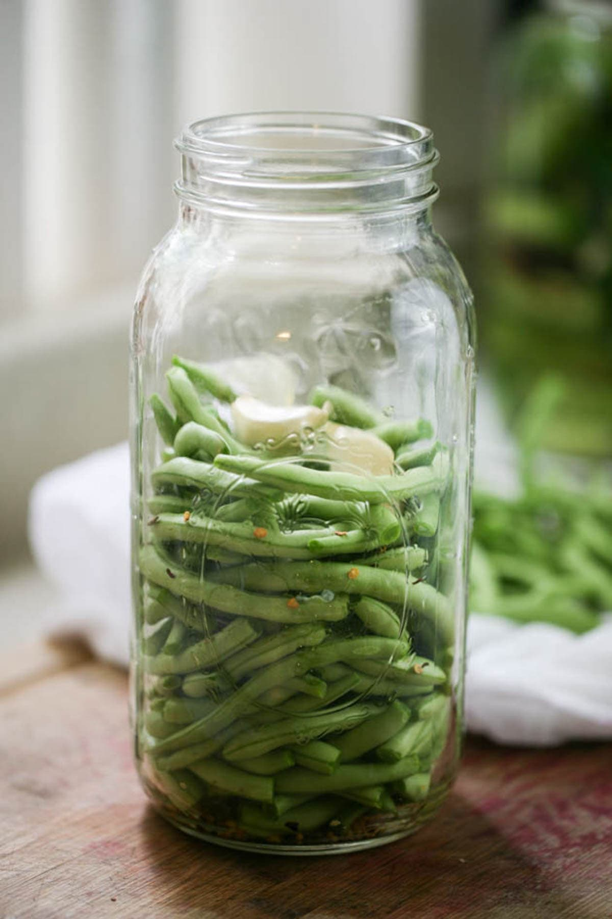 Adding garlic to the jar of green beans.