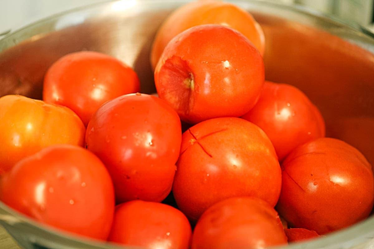 Blanching tomatoes before peeling them.