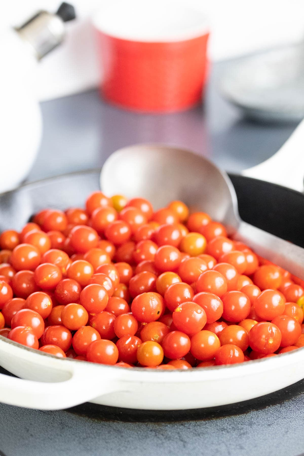 Adding cherry tomatoes to a a pan to cook before hot packing them in jars.