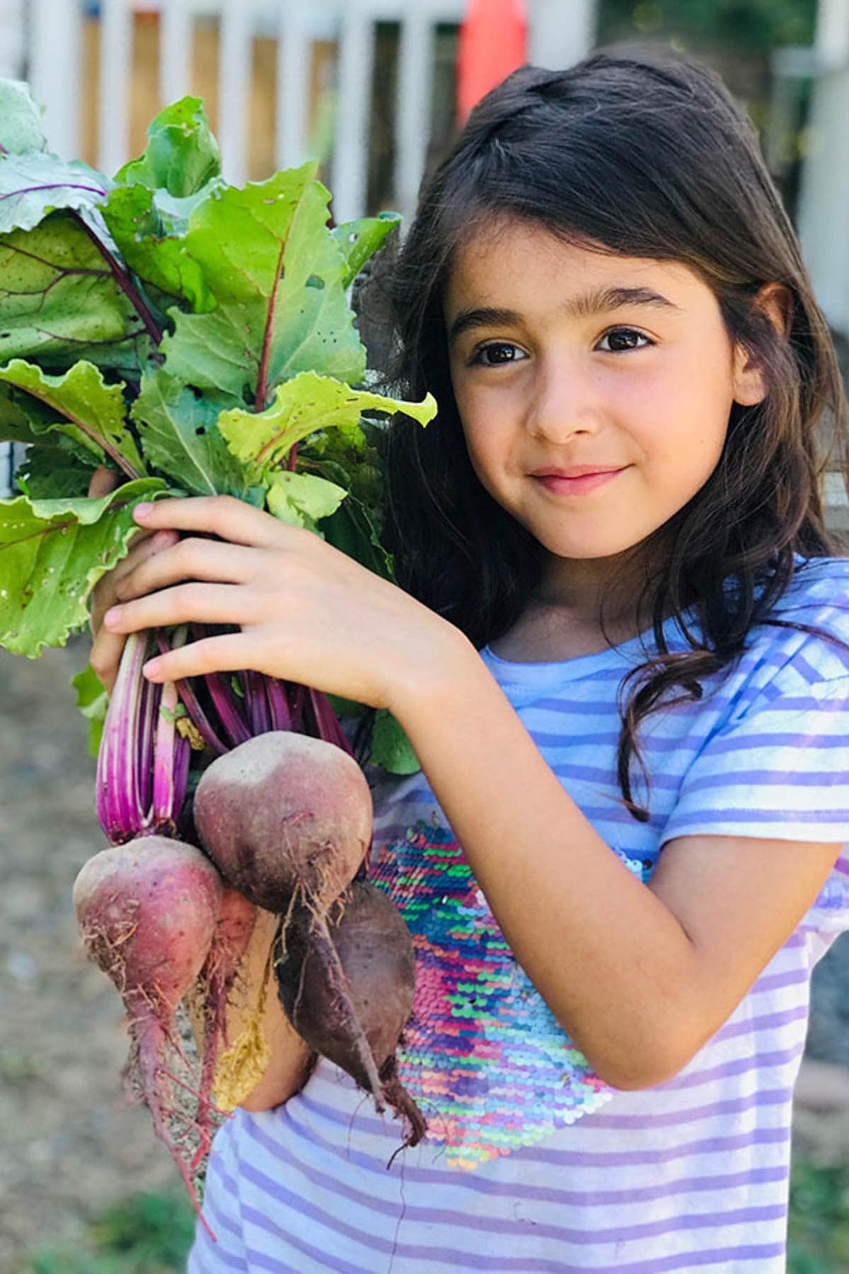 Nori holding fresh beets from the garden