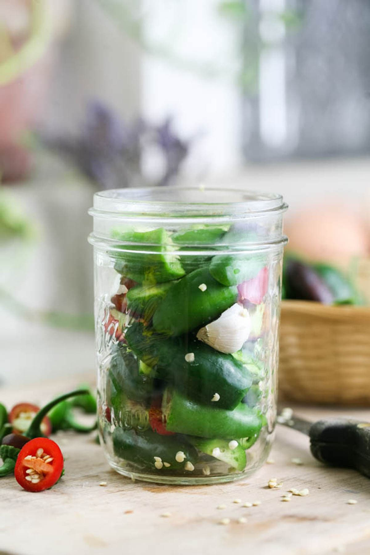 Packing the jar with jalapeno peppers.