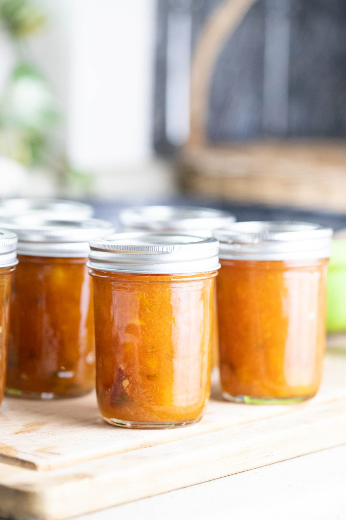 Jars with peach jalapeno jam ready for processing.